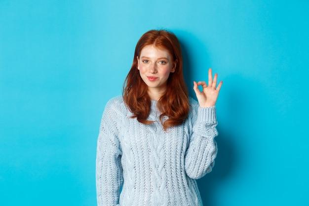 Zelfverzekerd roodharig meisje dat je verzekert, een goed teken toont en glimlacht, ja zegt, goedkeurt en akkoord gaat, over een blauwe achtergrond staat