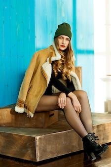 Zelfverzekerd sexy meisje in een bruine schapenvacht jas en een hoed met kousen zit op het podium en kijkt naar de camera naar de blauwe houten muur.