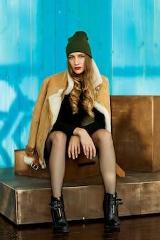 Zelfverzekerd sexy meisje in een bruine schapenvacht jas en een hoed met kousen zit op het podium en kijkt naar de camera op de blauwe houten muur. bovenkleding
