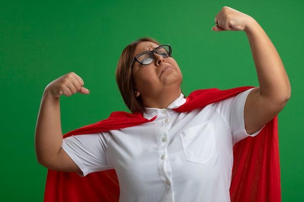 Zelfverzekerd superheld vrouwtje van middelbare leeftijd met een bril die sterk gebaar toont dat op groene achtergrond wordt geïsoleerd