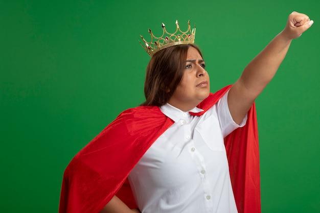 Zelfverzekerd superheldwijfje van middelbare leeftijd die kant bekijken die kroon dragen die vuist opheffen die op groene achtergrond wordt geïsoleerd