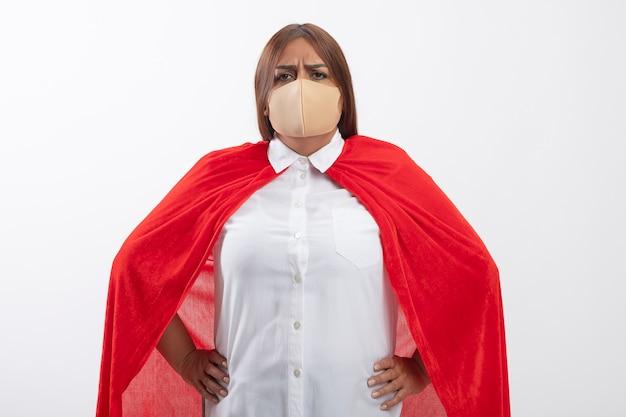 Zelfverzekerd superheldwijfje van middelbare leeftijd die medisch masker dragen dat handen op heup zet die op wit wordt geïsoleerd