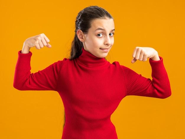 Zelfverzekerd tienermeisje dat naar de voorkant kijkt en een sterk gebaar doet dat op een oranje muur wordt geïsoleerd