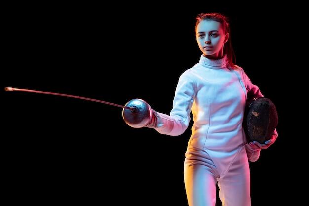 Zelfverzekerd. tienermeisje in hekwerkkostuum met in hand zwaard geïsoleerd op zwarte achtergrond, neonlicht. jong model oefenen en trainen in beweging, actie. copyspace. sport, jeugd, gezonde levensstijl.
