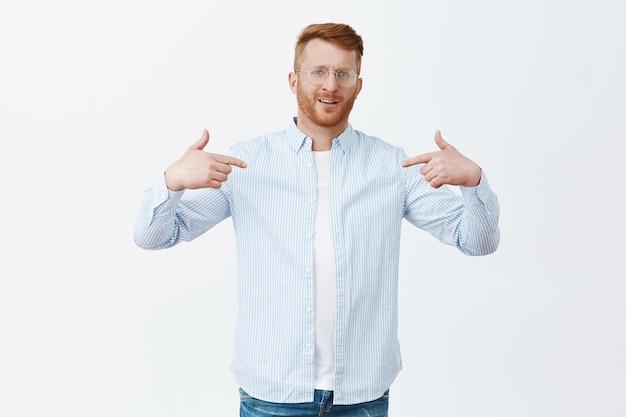 Zelfverzekerd trotse roodharige mannelijke ondernemer in shirt over t-shirt wijzend naar zichzelf en starend met trots, opscheppend over eigen prestaties, zelfverzekerd gevoel over grijze muur