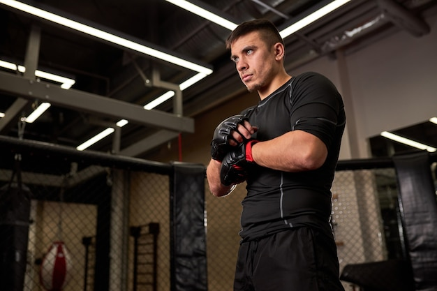 Zelfverzekerd uitziende man in zwarte kleding die vooruitkijkt en zich voorbereidt op vechten, handschoenen draagt. sport, fitness, boksconcept
