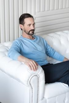 Zelfverzekerd voelen. goed uitziende serieuze bebaarde man zittend op een witte bank en zijn benen kruisen terwijl hij aan iets denkt