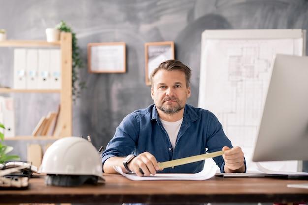Zelfverzekerd volwassen ingenieur meetlint houden over blauwdruk zittend aan tafel in zijn kantoor en werken