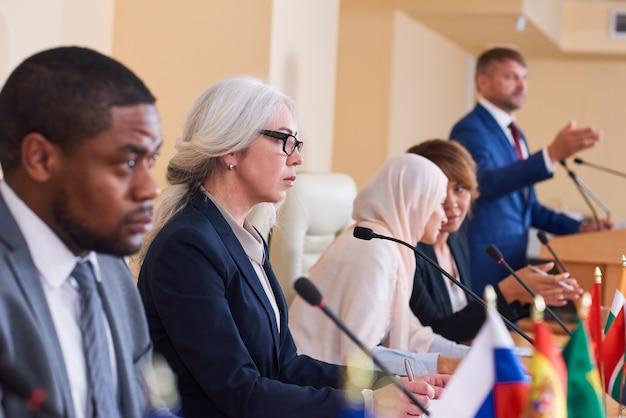 Zelfverzekerd volwassen vrouwelijke afgevaardigde in formalwear die in microfoon spreekt tijdens toespraak op conferentie