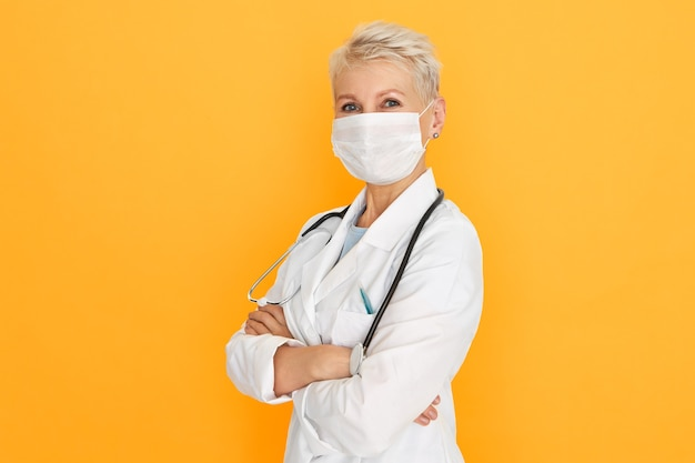 Zelfverzekerd volwassen vrouwelijke arts poseren tegen gele lege muur achtergrond, gekleed in witte medische jurk en beschermend chirurgisch masker, armen kruisen op haar borst. virussen, infecties en bacteriën