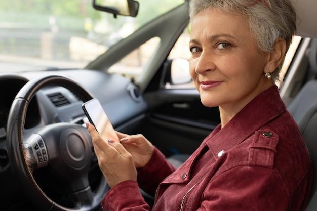 Zelfverzekerd volwassen zakenvrouw in stijlvolle jas chats met haar smartphone in de auto