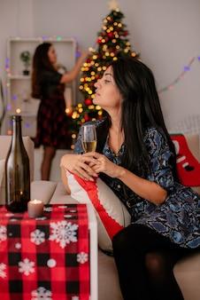 Zelfverzekerd vrij jong meisje drinkt glas champagne zittend op een stoel en kijken naar haar vriend versieren kerstboom genieten van kersttijd thuis