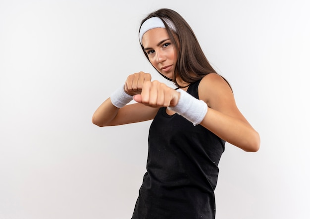 Zelfverzekerd vrij sportief meisje met hoofdband en polsband die boksgebaar doet geïsoleerd op een witte muur met kopieerruimte