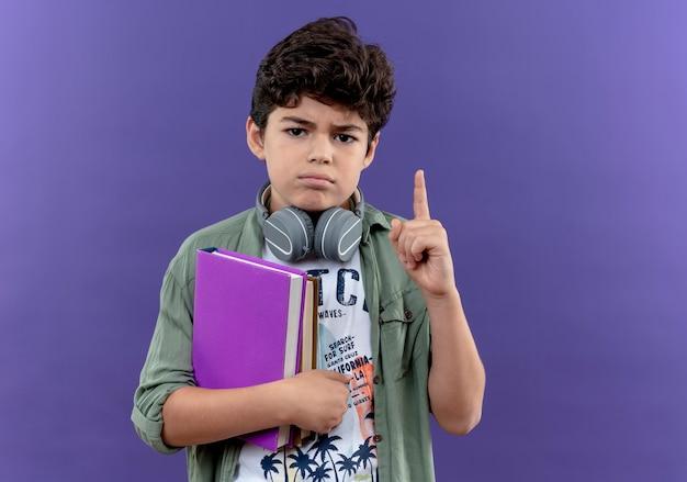Zelfverzekerd weinig schooljongen die hoofdtelefoons draagt die boeken en punten omhoog houdt
