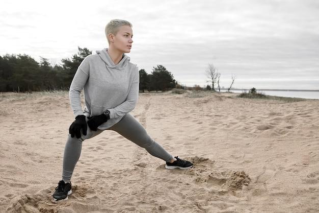 Zelfverzekerde aantrekkelijke jonge vrouwelijke atleet met kort blond haar