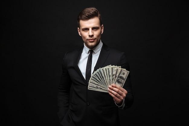 Zelfverzekerde aantrekkelijke jonge zakenman die een pak draagt dat geïsoleerd over een zwarte muur staat en geldbankbiljetten toont