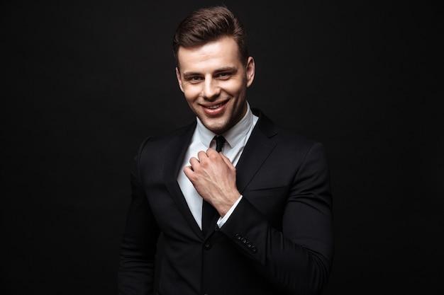 Zelfverzekerde aantrekkelijke jonge zakenman die een pak draagt dat geïsoleerd over een zwarte muur staat en naar de camera kijkt