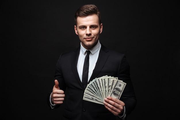 Zelfverzekerde aantrekkelijke jonge zakenman die een pak draagt dat geïsoleerd over een zwarte muur staat, geldbankbiljetten toont, duimen omhoog