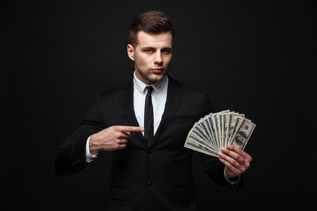 Zelfverzekerde aantrekkelijke jonge zakenman die een pak draagt dat geïsoleerd over een zwarte muur staat, geldbankbiljetten toont, wijzend