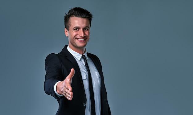 Zelfverzekerde aantrekkelijke jonge zakenman die een pak draagt dat geïsoleerd staat over een grijze achtergrond, met uitgestrekte hand voor begroeting.
