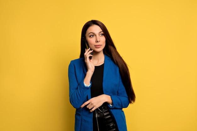 Zelfverzekerde aantrekkelijke jonge zakenvrouw in blauw jasje praten aan de telefoon