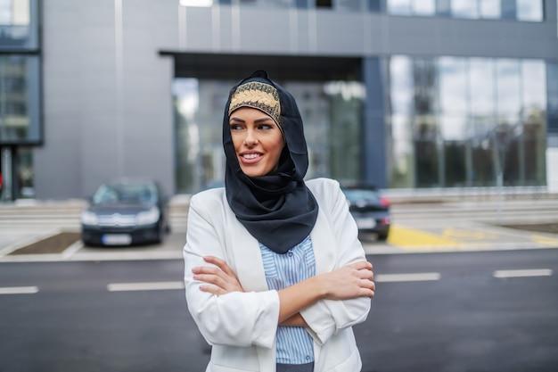 Zelfverzekerde aantrekkelijke stijlvolle moslim zakenvrouw staande voor corporate gebouw met armen gevouwen en wegkijken.