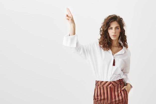 Zelfverzekerde aantrekkelijke vrouw die vinger omhoog wijst