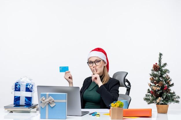 Zelfverzekerde aantrekkelijke vrouw met kerstman hoed en bril zittend aan een tafel en bankkaart houden en stilte gebaar maken op kantoor