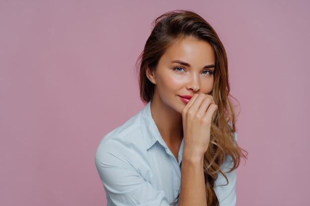 Zelfverzekerde aantrekkelijke vrouw met lang haar, houdt de hand op de lippen, gekleed in een blauw shirt