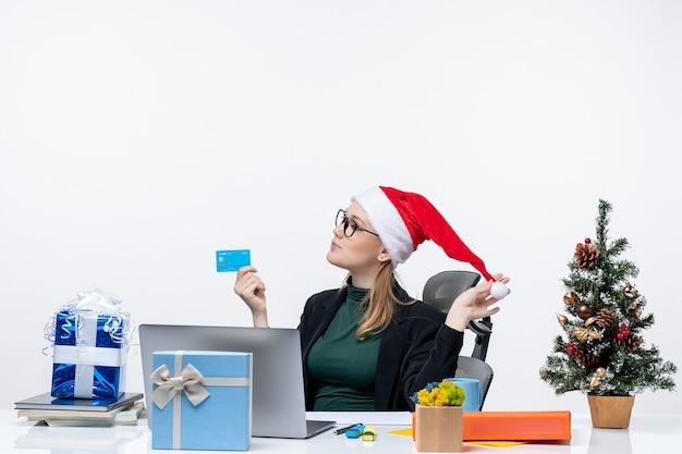 Zelfverzekerde aantrekkelijke vrouw speelt met haar hoed van de kerstman en het dragen van een bril aan een tafel zitten en bankkaart in het kantoor te houden