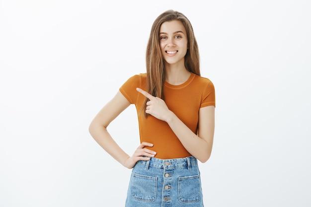 Zelfverzekerde aantrekkelijke vrouw wijzende vinger naar links, uitnodigend voor online cursussen of winkel te bezoeken