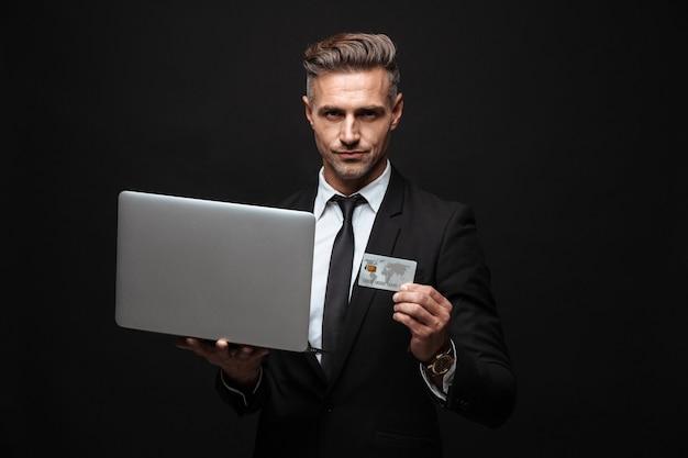 Zelfverzekerde aantrekkelijke zakenman die een pak draagt dat geïsoleerd over een zwarte muur staat, een laptop gebruikt en een plastic creditcard toont