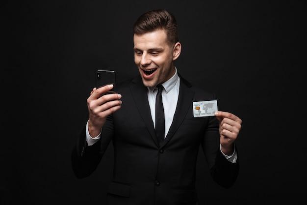 Zelfverzekerde aantrekkelijke zakenman die een pak draagt dat geïsoleerd over een zwarte muur staat, een mobiele telefoon gebruikt en een plastic creditcard toont