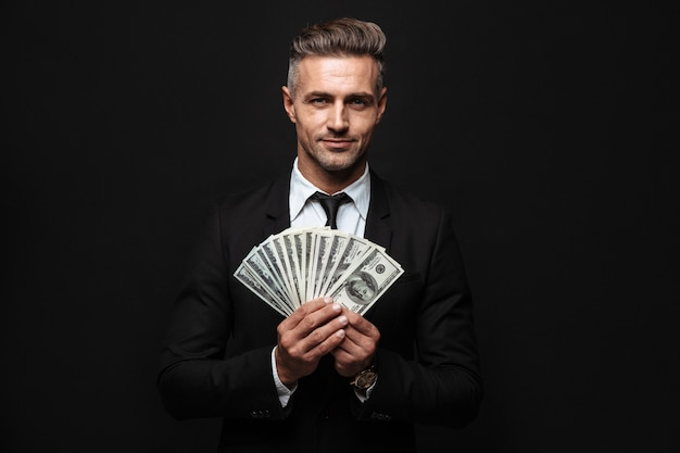 Zelfverzekerde aantrekkelijke zakenman die een pak draagt dat geïsoleerd over een zwarte muur staat en geldbankbiljetten toont