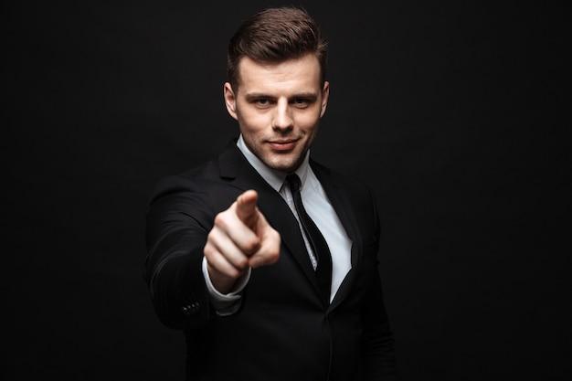 Zelfverzekerde aantrekkelijke zakenman die een pak draagt dat geïsoleerd over een zwarte muur staat en met de vinger naar de camera wijst