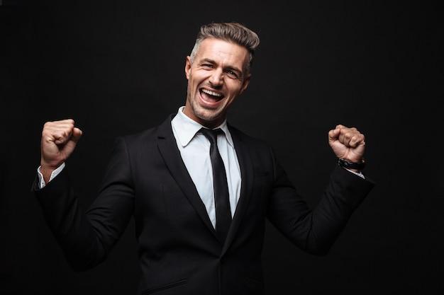 Zelfverzekerde aantrekkelijke zakenman die een pak draagt dat geïsoleerd over een zwarte muur staat en succes viert