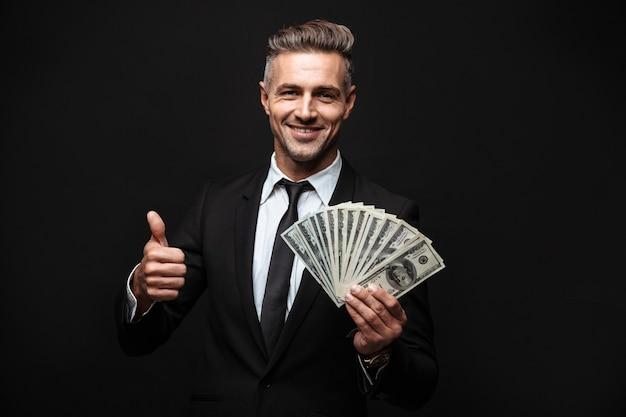 Zelfverzekerde aantrekkelijke zakenman die een pak draagt dat geïsoleerd over een zwarte muur staat, geldbankbiljetten toont, duimen omhoog