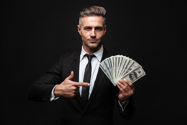 Zelfverzekerde aantrekkelijke zakenman die een pak draagt dat geïsoleerd over een zwarte muur staat, geldbankbiljetten toont, met de vinger wijst Premium Foto
