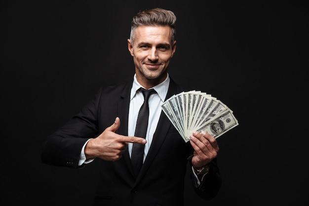 Zelfverzekerde aantrekkelijke zakenman die een pak draagt dat geïsoleerd over een zwarte muur staat, geldbankbiljetten toont, met de vinger wijst