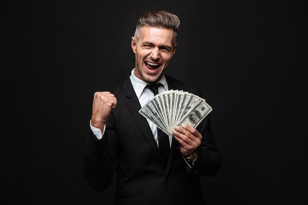 Zelfverzekerde aantrekkelijke zakenman die een pak draagt dat geïsoleerd over een zwarte muur staat, geldbankbiljetten toont, viert Premium Foto