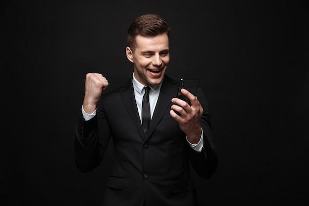 Zelfverzekerde aantrekkelijke zakenman die een pak draagt dat geïsoleerd over een zwarte muur staat, mobiele telefoon gebruikt, succes viert