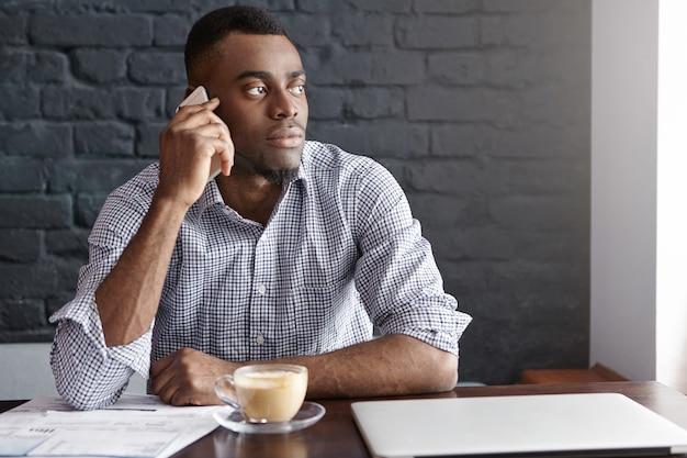 Zelfverzekerde afrikaanse ceo van groot financieel bedrijf zakelijke telefoontjes tijdens koffiepauze