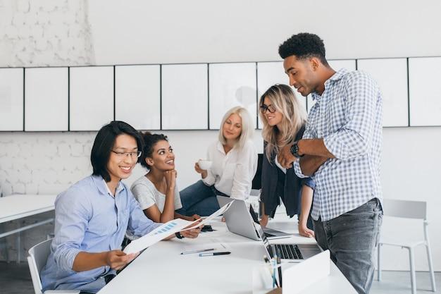 Zelfverzekerde afrikaanse man in stijlvol polshorloge poseren in kantoor, tijdens een gesprek met aziatische webontwikkelaar. indoor portret van langharige vrouw met laptop iets bespreken met chef en secretaris.