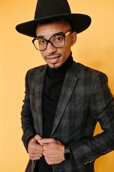 Zelfverzekerde afrikaanse man in zwarte kleding en trendy polshorloge poseren. binnenfoto van knappe mulatkerel in glazen die op oranje muur wordt geïsoleerd.