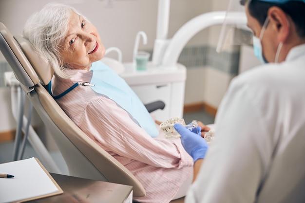 Zelfverzekerde arts-cosmetologist die tandmodel voor hogere vrouw in de kliniek toont showing