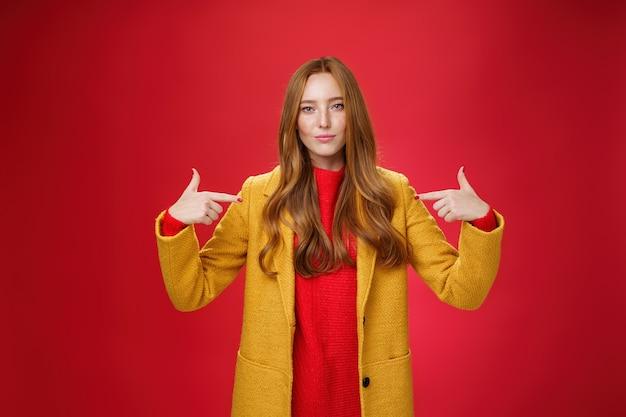 Zelfverzekerde assertieve en optimistische charmante vrouwelijke ondernemer met rood haar in gele jas die naar zichzelf wijst, trots opschept over eigen succes of bereid is kandidaat te zijn en zelfverzekerd glimlacht.