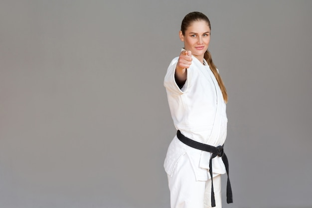 Zelfverzekerde atletische jonge vrouw in witte kimono en zwarte gordel staan, wijzende vinger en kijken naar de camera met een glimlach. japans vechtsportenconcept. indoor studio-opname, geïsoleerd op een grijze achtergrond