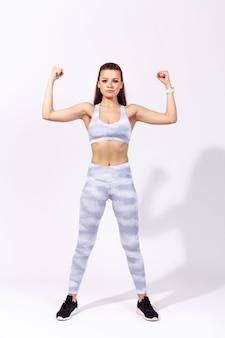 Zelfverzekerde atletische vrouw van volledige lengte die haar sterke buikspieren en biceps toont en handen omhoog steekt