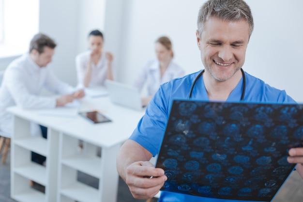 Zelfverzekerde attente optimistische neuroloog die in het ziekenhuis werkt en mrt-scanresultaten onderzoekt terwijl collega's erachter hun mening delen