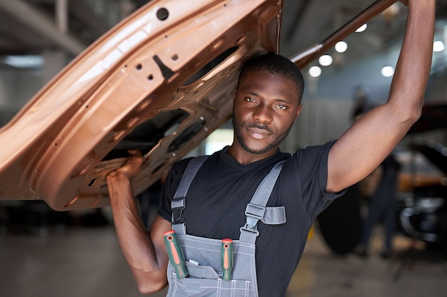 Zelfverzekerde automonteur houdt een apart deel van de auto vast, gaat het repareren op de werkplek, houdt het vast